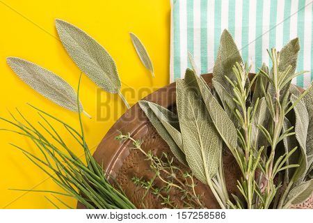 Old Copper Dish With Variety Of Fresh Herbs On Blue Striped  Folded Towel And Yellow Background.