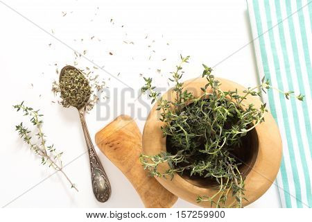Fresh Thyme In  Wooden Mortar With Pestle And Dry On Spoon, On Withe Background.