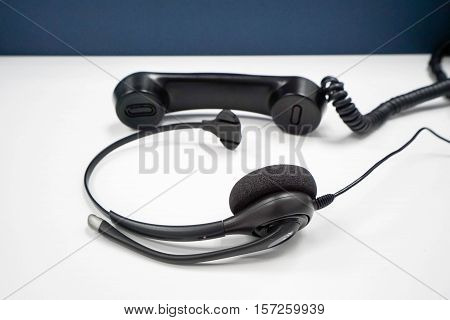 headphone of IP phone with call center headset on office desk