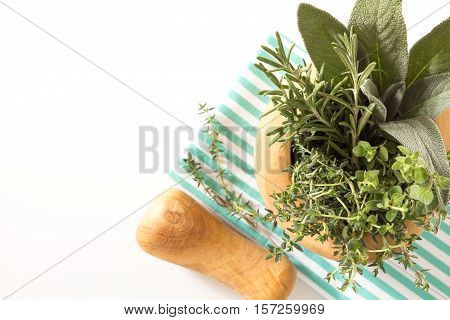 Fresh Herbs Bouquet In Wooden Mortar On Folded Kitchen Towel, On White Background.