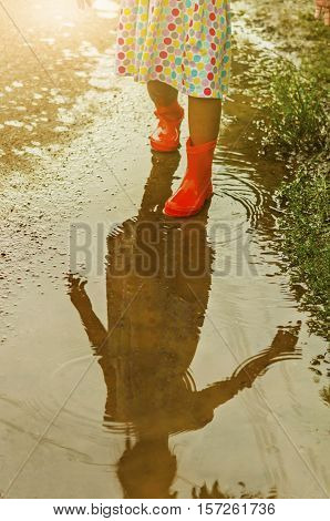 Child wearing orange rain boots walking into a puddle. Close up