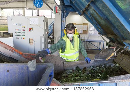 Sofia Bulgaria - May 26 2016: Glass waste worker is recycling glass bottles in a recycling facility. Different glass packaging bottle waste. Glass waste management.