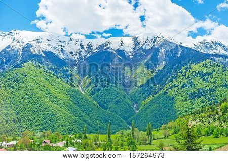 The farm lands in valley surrounded by mountains with green slopes and narrow waterfalls Upper Svaneti Georgia.