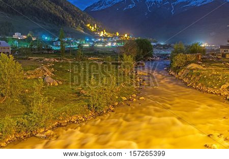 The evening view of Mestia with the brightly illuminated Mestiachala river and the mountains in sade on the background Upper Svaneti Georgia.