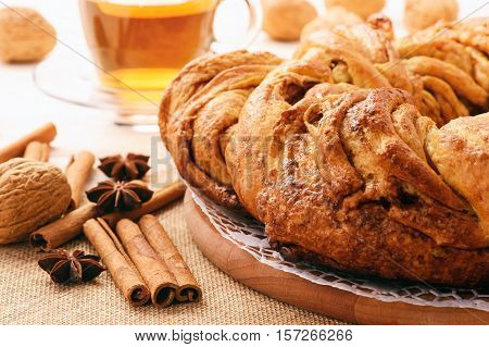 Braided cinnamon roll cake on wooden background.