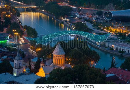 Evening scene in Tbilisi (Georgia) historical centrum. Illuminated bridge of Peace and Kura river in the middle of composition.