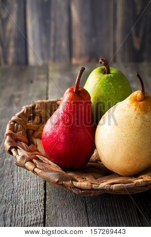 Red green yellow sweet pear and an apple on a plate made of rattan on a dark background. Selective fokus.Rustik style.