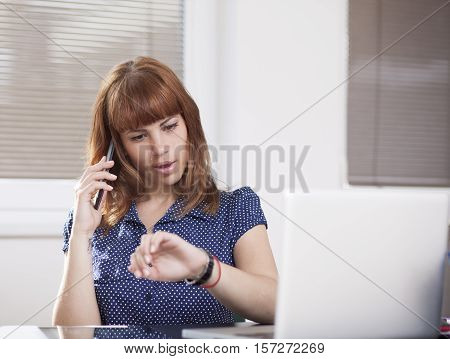 Nice girl in working environment is talking at the phone and watching time, she is late for something