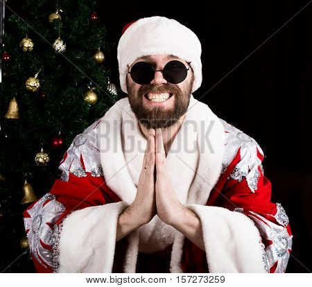 bad rastoman Santa Claus smiles and making hands sign namaste on the background of Christmas tree.