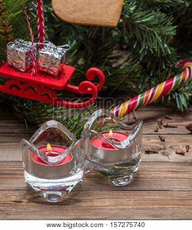 Christmas tree branches and lighted candels on a wooden background