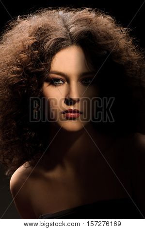 Brunette girl with a curly hairstyle modern make-up and carnivore look
