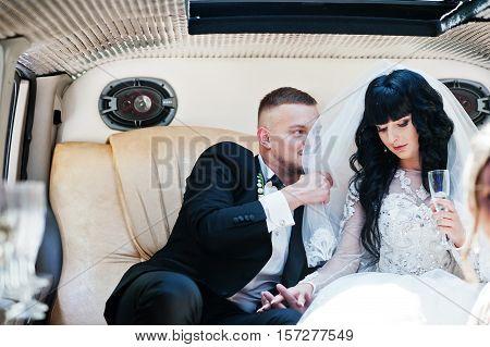 Amazing Wedding Couple Inside Elegance Limousine At Their Awesome Wedding Day.