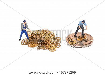 Miniature people repairing clockwork. Teamwork. Help in the work. Working employees. A pile of gear. Gears and clockwork isolated. Yellow cogs.