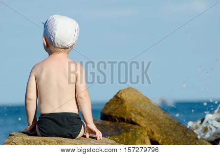 Little boy sitting with his back to a rock on the seashore in swimming trunks blue sky space for text
