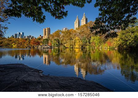 Fall in Central Park at The Lake. Cityscape sunrise view with colorful Autumn foliage on the Upper West Side. Manhattan, New York City