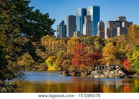 Fall in Central Park at The Lake with Upper West Side skyscrapers. Cityscape sunrise view with colorful Autumn foliage. Manhattan, New York City