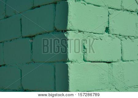 Outward corner of the green wall. Brick wall.