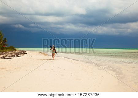 Young lady photographer in bikini walks on the caribbean tropical island sandy beach, Cuba vacation