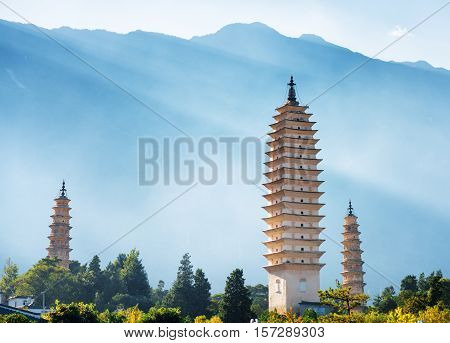 The Three Pagodas of Chongsheng Temple near Dali Old Town Yunnan province China. Scenic mountains are visible in background. Ancient pagodas are a popular tourist destination of Asia.