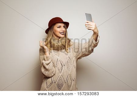 Beautiful modern young blonde Caucasian woman in autumn outfit taking a selfie. Teenage girl in beige sweater, dark red floppy hat and dark lipstick photographing herself.