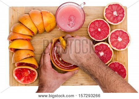 Hands Of A Man Squeezing Fresh Ruby Grapefruit