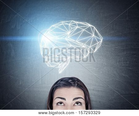 Close up of a girl with black hair looking at a brain hologram glowing with blue light. Concept of a good idea. Toned image