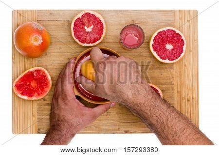 Man Squeezing Ruby Grapefruit Halves
