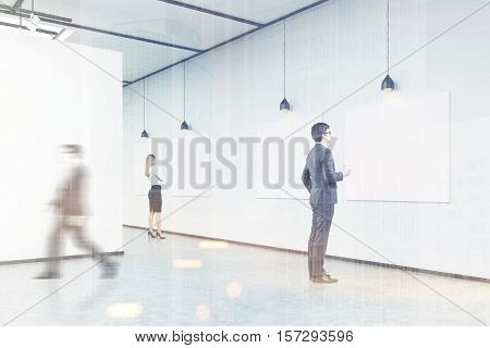 Side view of a man with a paper cup of coffee looking at a picture on white wall. His colleague is passing by. Blond girl in background. Concept of cultural event. 3d rendering. Mock up. Toned image