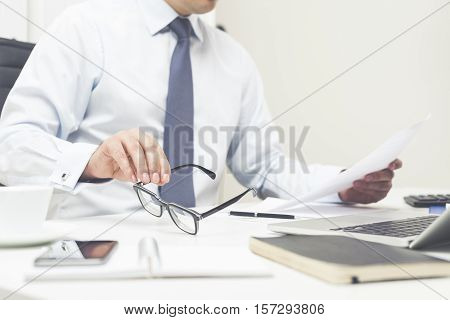 Close up of businessman's hands. He is reading a document and holding his glasses in the second hand. Concept of lawyer's work