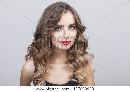 Close up of young woman with long brown hair who is looking at the camera with interest in her eyes as if she is expecting that the viewer would do something funny