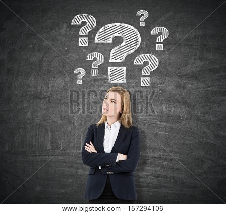 Blond woman is standing with her arms crossed near a blackboard with question mark sketches drawn above her head