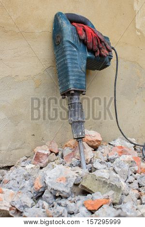 tool jackhammer standing on a wall of stone bricks