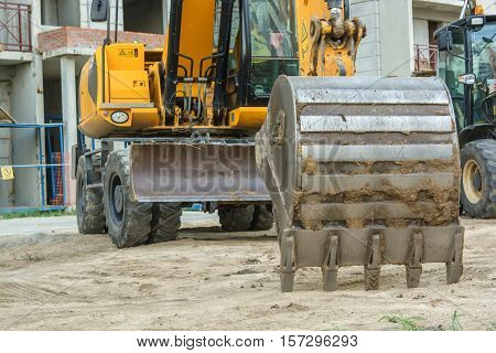 Pair of backhoe excavators standing at construction site