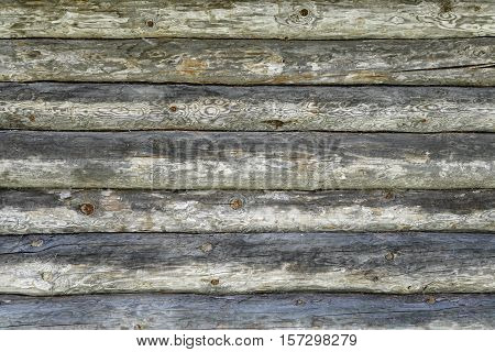 Old Hand Hewn Natural Log Cabin Wall Facade Fragment Texture. Rustic Log Wall Horizontal Timber Grey Background. Fragment Of Unpainted Gray Wooden Debarked Logs Barn Wall Planed House Wood Structure