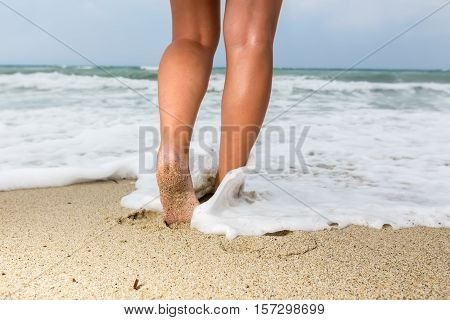 Closeup Of A Man's Bare Feet Walking At A Beach, With A Wave's Edge Foaming Gently Beneath Them, Ton