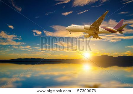 Airplane in the sky on the lake with reflection at sunset.