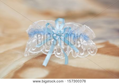 Decorated wedding garter on beige background. Marriage concept