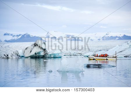 Tourists on amphibious vehicle taking a cruise around the Jokulsarlon glacier lake where icebergs melting from the Vatnajokull glacier and float out to the Atlantic ocean