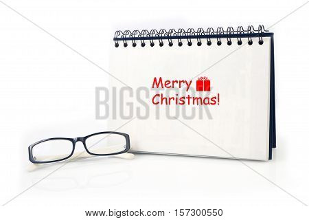 Desktop Loop wire binding book with Merry Christmas text and modern eyeglasses on isolated white background.