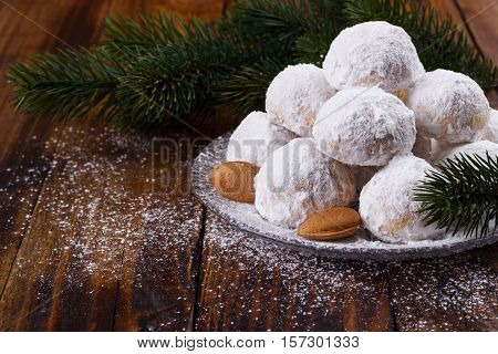 Traditional Christmas cookies with almonds on dark wooden background