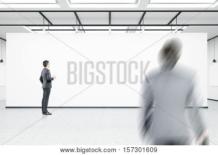 Side view of a man looking at a blank wall. His colleague is entering the building. No furniture in the room. Concept of new workplace. 3d rendering. Mock up.