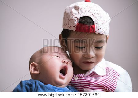 Duo portrait of sibling with little yawning baby