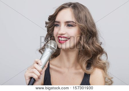 Close up of a beautiful girl with long wavy hair who is smiling and holding a large microphone. Concept of a rising star