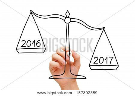 Hand drawing scale concept with marker on transparent wipe board isolated on white. Year 2017 is better than 2016.