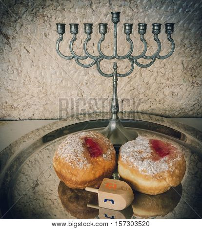 Festive sweet donuts, menorah and dreidel are traditional symbols of Hanukkah holiday. Selective focus. Image toned for inspiration of retro style