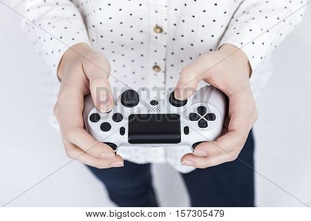 Close up of a girl in white polka dot shirt holding a video game controller with both hands. Concept of woman gamer