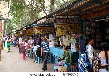 KOLKATA, INDIA - FEBRUARY 11: Students check out books at an old street side book stall at College Street Book Market in Kolkata, India on February 11, 2016.