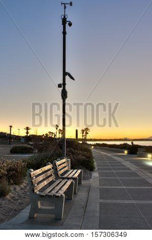 Pedestrian resting benches along Ventura Boardwalk at sunrise.