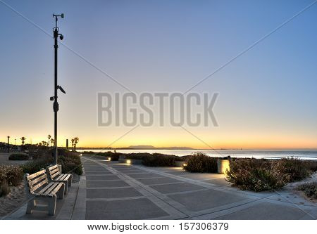 Panoramic view of wooden benches along Ventura beach boardwalk at sunrise.