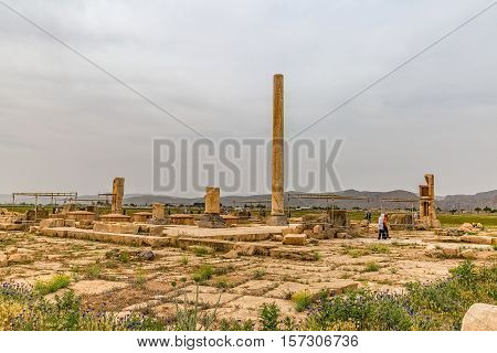 PASARGAD, IRAN - MAY 4, 2015: The group of tourists with the tour guide checking out the archaeological site of the old city.